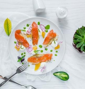 Filete de salmón ahumado con salsa verde dentro de un plato blanco.