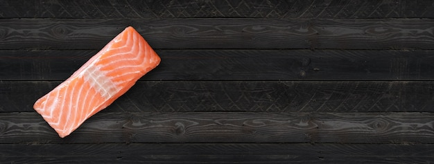 Filete de salmón aislado sobre fondo de tablero de madera negra. vista superior. banner horizontal
