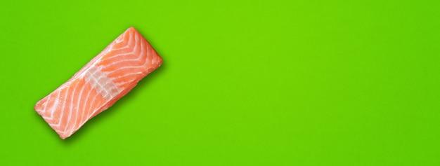 Filete de salmón aislado sobre fondo verde. vista superior. banner horizontal