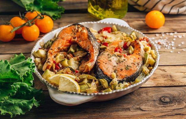 Filete de salmón al horno con verduras sobre fondo rústico de madera. concepto de comida sana. enfoque selectivo