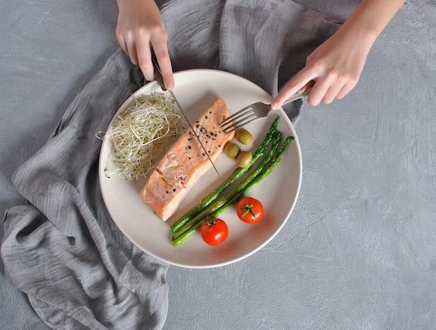 Filete de salmón cocido con aceitunas, tomates cherry y espárragos