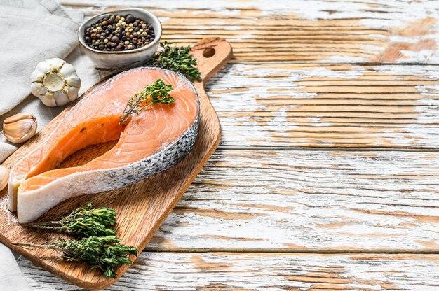 Filete de salmón crudo fresco con pimienta y tomillo. espacio de madera blanca. vista superior. copia espacio
