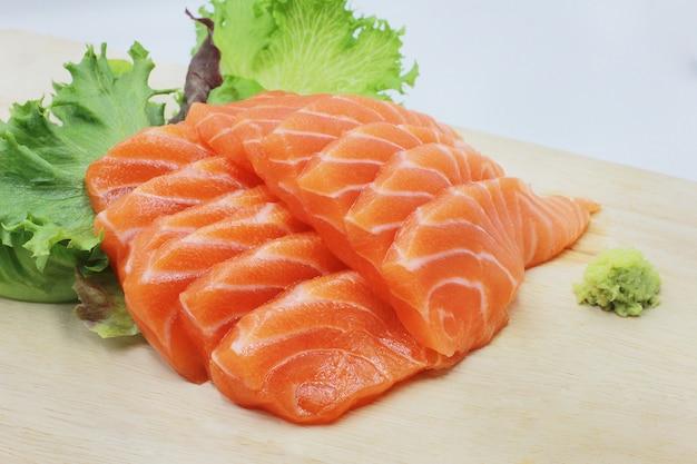 Filete de salmón crudo fresco con verduras en madera.