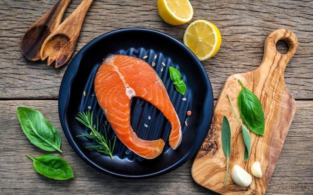 Filete de salmón crudo en la placa negra con los ingredientes en fondo de madera. Foto Premium