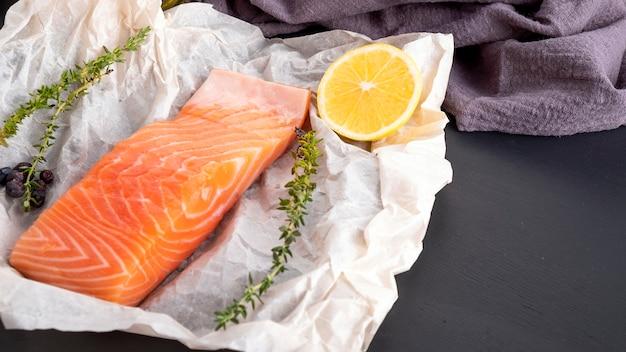 Filete de salmón crudo sobre pergamino con especias. espacio de texto