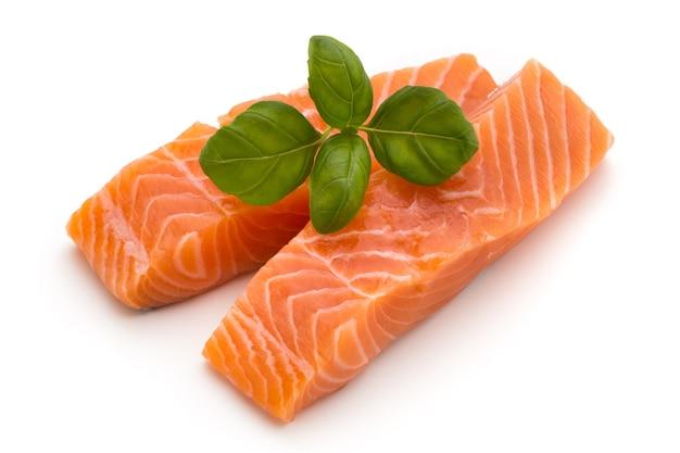 Filete de salmón fresco con albahaca sobre fondo blanco.