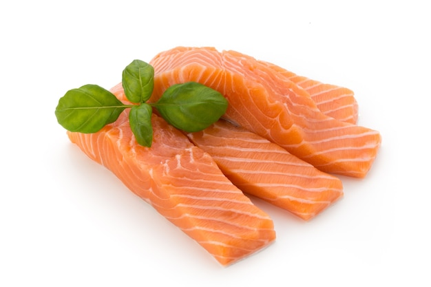 Filete de salmón fresco con albahaca sobre la superficie blanca.