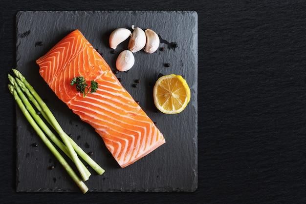 Filete de salmón fresco crudo con hierbas e ingredientes, en placa de piedra negra