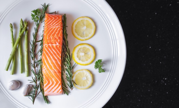 Filete de salmón fresco crudo con hierbas e ingredientes, en plato blanco y mesa negra