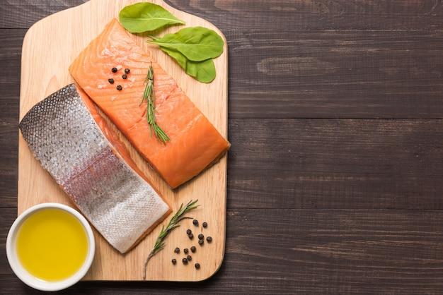 Filete de salmón fresco con especias en mesa de madera