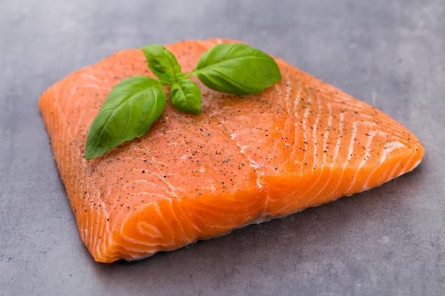 Filete de salmón fresco con especias sobre la superficie gris.
