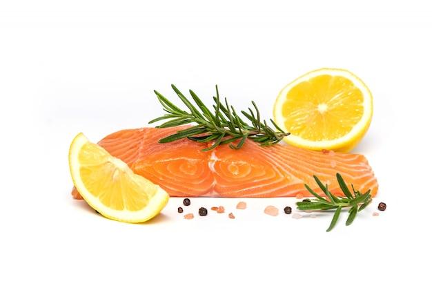 Filete de salmón fresco con hierbas y limón aislado