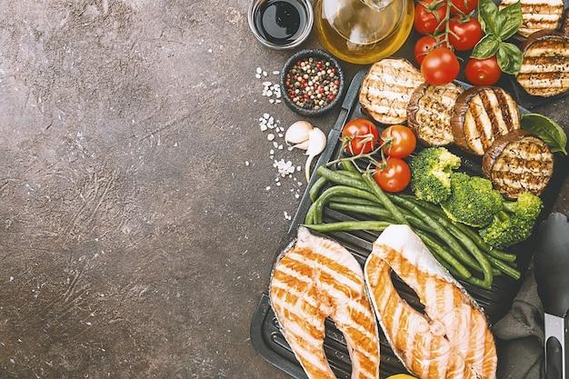 Filete de salmón a la parrilla de alimentos saludables, pollo y verduras sobre una superficie oscura, vista superior