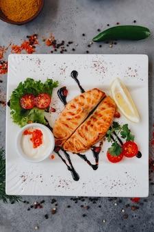 Filete de salmón a la parrilla y ensalada en un plato. vista superior horizontal