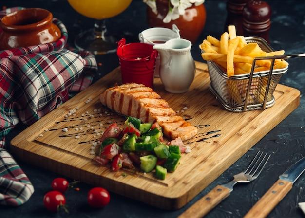 Filete de salmón a la parrilla con papas fritas, mayonesa, salsa de tomate y ensalada fresca