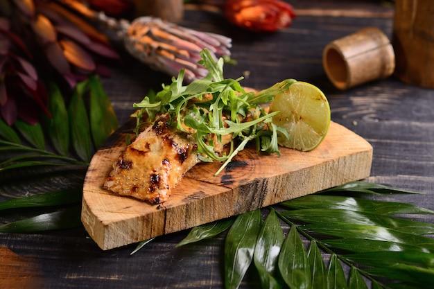Filete de salmón a la plancha con lima y rúcula. en una tabla de madera
