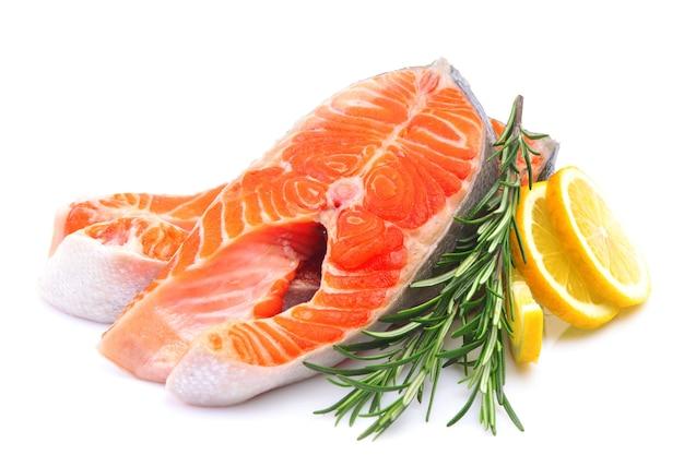 Filete de salmón con rodajas de limón aislado sobre fondo blanco.