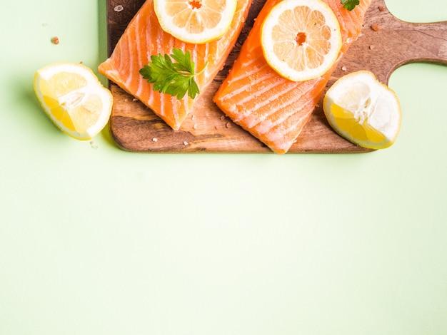 Filete de salmón sobre tabla de madera con rodajas de limón