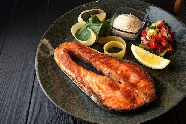 Filete de salmón con verduras, limón y salsa, sobre un fondo de madera negra