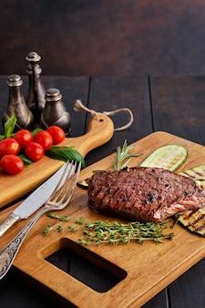 Filete de ternera y calabacín servido con tomate fresco cereza y albahaca sobre tabla para cortar madera