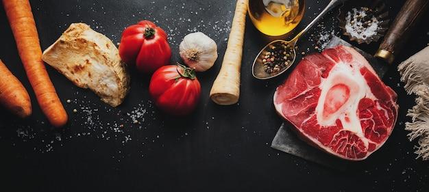 Filete de ternera de carne cruda con especias de huesos y verduras sobre superficie oscura
