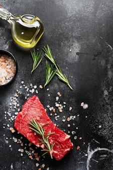 Filete de ternera cruda con especias, cebollas y romero sobre pizarra oscura u hormigón.