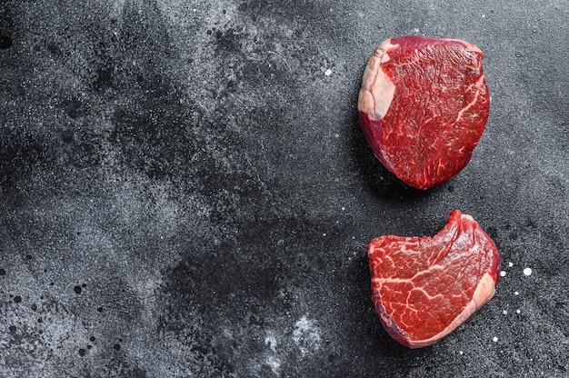 Filete de ternera cruda filete de solomillo. fondo negro. vista superior. copie el espacio.