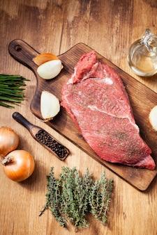 Filete de ternera cruda sobre tabla de cortar de madera junto a cebollas y sazonado con romero. preparación de carnes. ingredientes naturales.