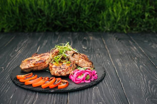 Un filete de ternera con especias y verduras, sobre una mesa de madera