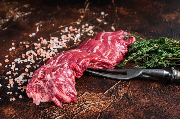 Filete de ternera de falda machete crudo en tenedor de carne. fondo oscuro. vista superior.