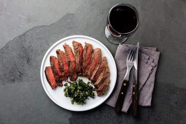 Filete de ternera medio raro en plato blanco, copa de vino tinto