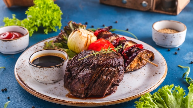 Filete de ternera a la parrilla especias y verduras en un plato. jugosas verduras de carne.