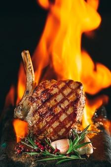 Filete de ternera a la parrilla con llamas sobre superficie oscura