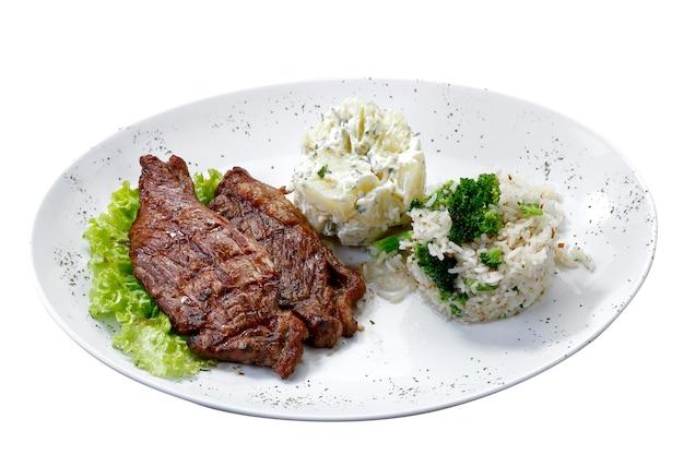 Filete de ternera con patatas y arroz en fondo blanco aislado