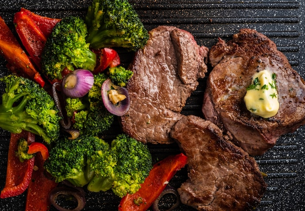 Filete de ternera a la plancha con mantequilla de ajo y verduras. carne con pimiento asado, brócoli y cebolla.