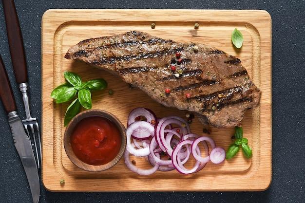 Filete de ternera a la plancha con salsa de tomate y cebollas rojas encurtidas sobre una tabla de madera. vista desde arriba.