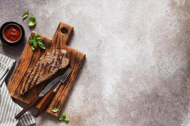 Filete de ternera a la plancha con salsa de tomate sobre una tabla de madera sobre un fondo de hormigón.