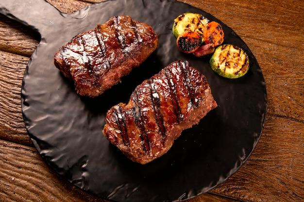 Filete de ternera en rodajas a la parrilla en tabla de cortar en tablero negro sobre la mesa de madera.