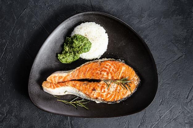 Filete de trucha a la parrilla con arroz y espinacas. mariscos saludables. fondo negro. vista superior