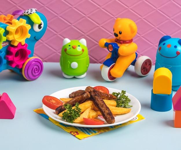 Filetes de carne frita con papas rodeadas de juguetes