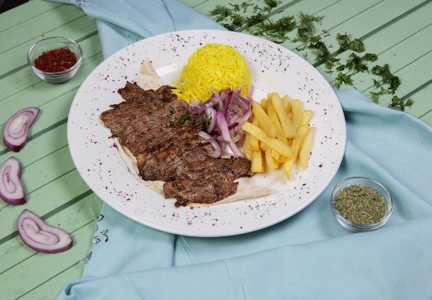 Filetes de carne con papas fritas y guarnición de arroz