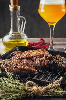 Filetes de carne a la parrilla en una sartén y un vaso de cerveza