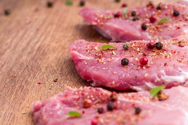 Filetes de cerdo crudos espolvoreados con especias y hierbas