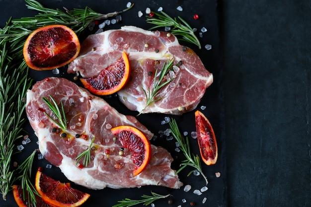 Filetes de cerdo crudos con romero y naranja marinados en una tabla de piedra.