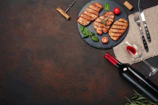 Filetes de cerdo a la parrilla en piedra con botella de vino, copa de vino, cuchillo y tenedor sobre fondo oxidado