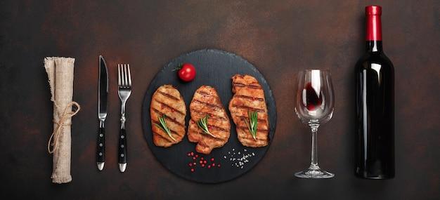 Filetes de cerdo a la plancha sobre piedra con botella de vino, copa de vino, cuchillo y tenedor sobre fondo oxidado. vista superior con espacio para su texto.