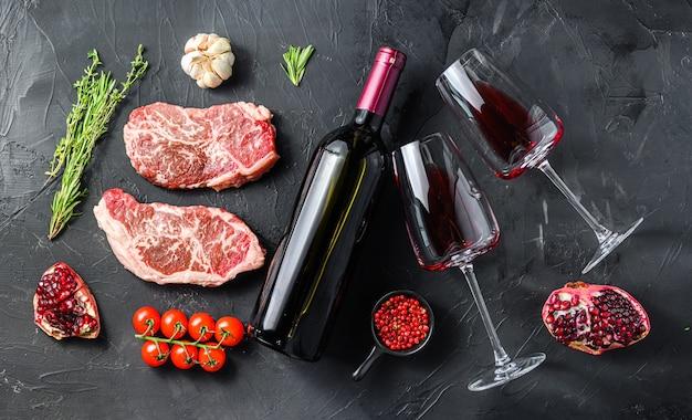 Filetes crudos de hoja superior con condimentos de hierbas cerca de la botella de vino tinto