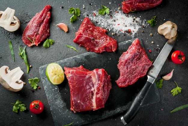 Filetes de lomo de carne cruda fresca en una tabla de cortar de pizarra en la mesa de piedra negra. con especias (sal, pimienta), ajo y hierbas - perejil y estragón. copia espacio vista superior