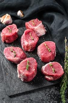 Filetes de medallón de cerdo crudo con pimiento y tomillo