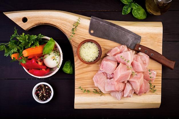Filetes de pechuga de pollo cruda en tabla de cortar de madera con hierbas y especias. vista superior